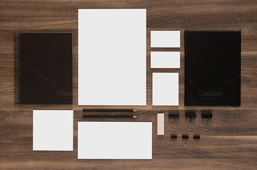 Set of branding mockup on brown wooden desk. Blank business cards with documents, paperclips and black notepads.