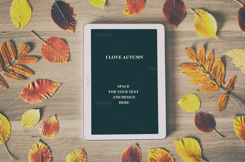 White tablet on a wooden table with colorful autumn leaves, business concept with space for text, advertising, and for any other design. Flat lay, top view.