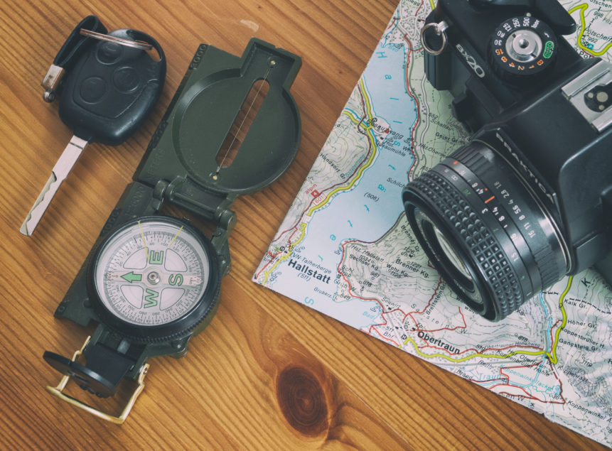 travel map, car key, compass and camera