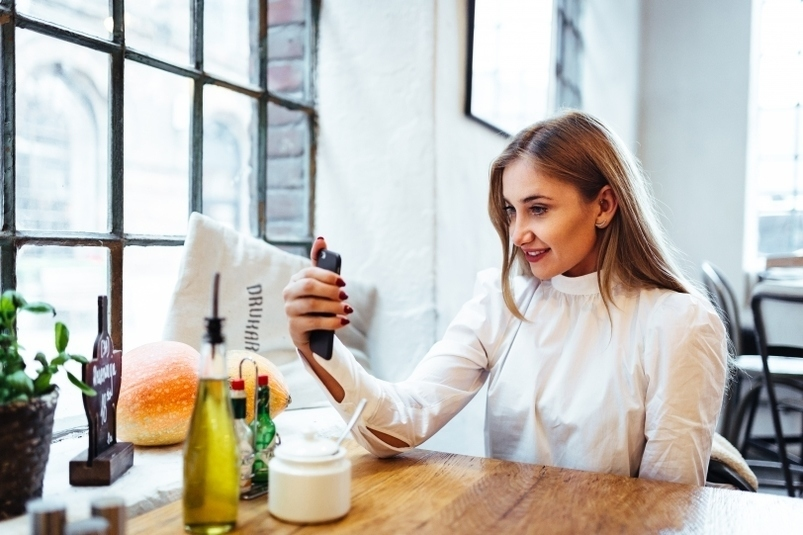 girl-taking-selfie-using-smartphone-at-the-restaurant-2